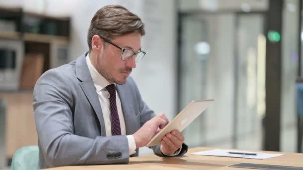 Seriózní profesionální podnikatel používající tablet v kanceláři