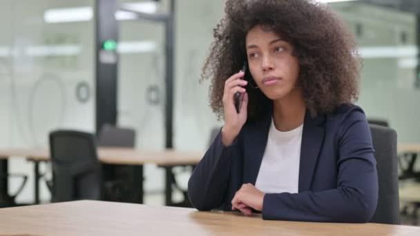 Wütende junge afrikanische Geschäftsfrau spricht auf Smartphone