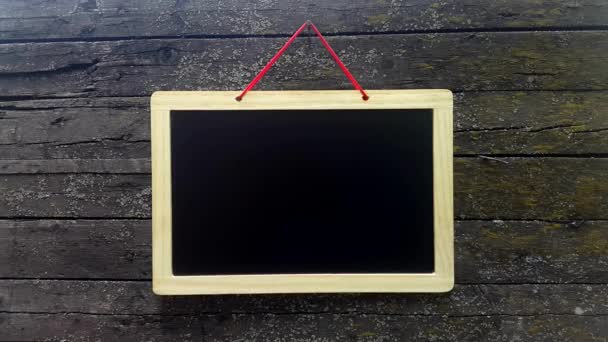 Blank advertising board. Empty black board against the background wooden wall