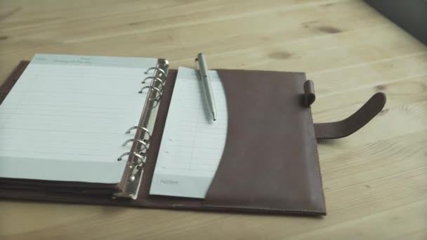 Krásné zblízka záběr otevřít elegantní světle hnědé kožené pouzdro poznámkový blok kniha denní plánovač kulka deník na dřevěném stole
