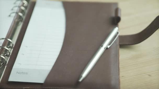 Krásné zblízka záběr otevřít elegantní světle hnědé kožené pouzdro denní plánovač poznámkový blok blok kulka deník na dřevěném stole