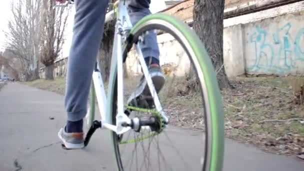 Man in sport pants rides a bike with green tyres slowly, healthy lifestyle, outdoor activity