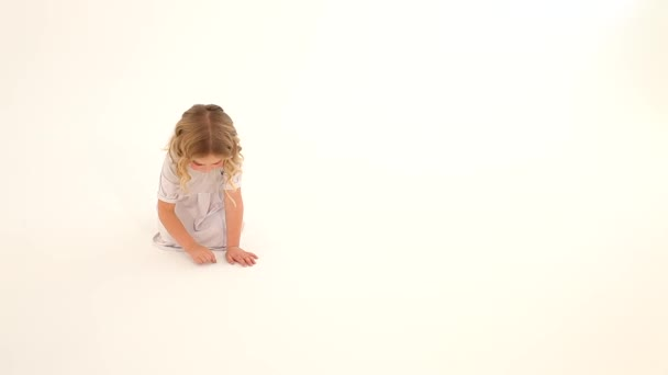 Dítě batole dítě dívka růžové tváře kudrnaté blond vlasy bílé šaty sedí kreslení srdce prsty na podlaze bílé pozadí