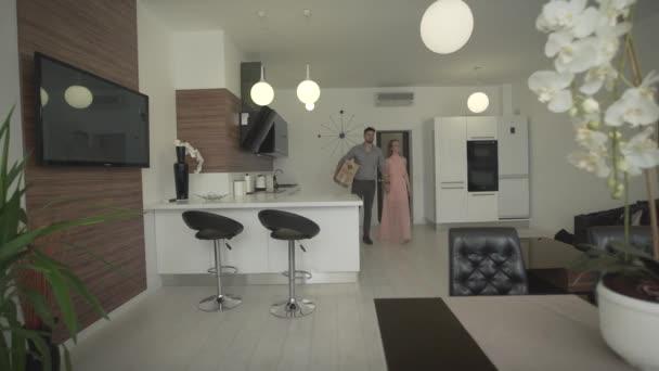 Mladý šťastný vzrušený pár pohybující se v novém moderním trendy byt hledá kolem krásné design interiéru v 4k záběr