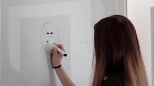 Junges Mädchen mit langen Haaren zeichnet ein glückliches Smiley-Gesicht mit Permanentmarker auf weißem Brett