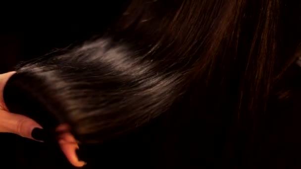 Nahaufnahme schwarzer Hintergrund Aufnahme der Frau Hand drehen schön begradigt glänzende Schokolade brünett dunkle Farbe Haare