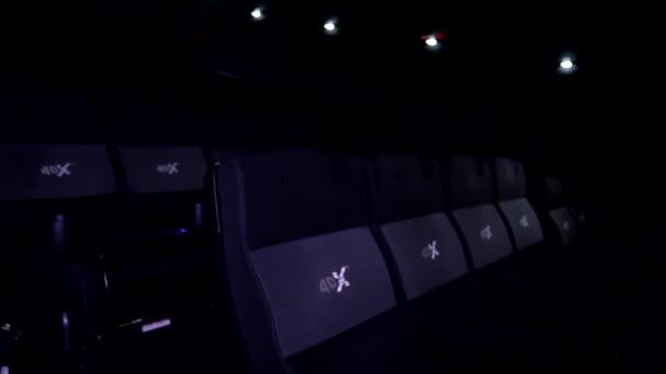 Niedrige Winkel Nahaufnahme auf Kino Kino bequeme schwarze Stuhlreihe bewegt sich in 3D-4D-Effekt in den dunklen Raum