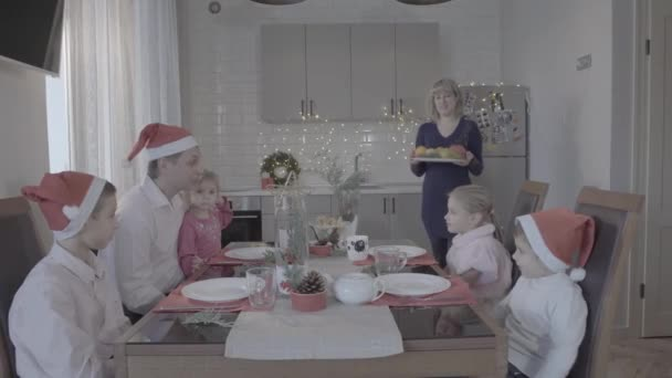 Lovely excited family of six enjoy festive Christmas dinner in amazing cozy kitchen celebration armosphere in Santa hats