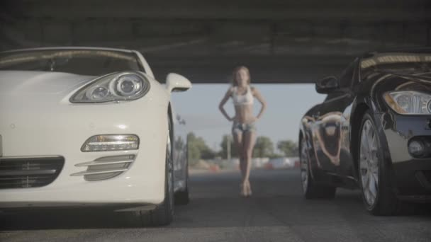 Close up shot of two new sport racing modern cars ready to start with attractive sexy young fit woman in the background