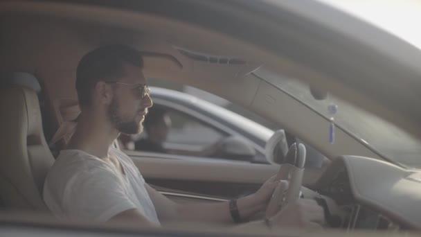 Atraktivní mladý tetovaný pohledný muž v slunečních brýlích sedí v luxusním sportovním závodním autě naproti soupeři připraven začít