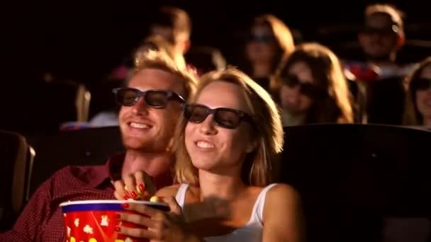 Eine Gruppe junger glücklicher aufgeregter attraktiver männlicher Freundinnen isst Popcorn und genießt das 3D-4d-Actionkino