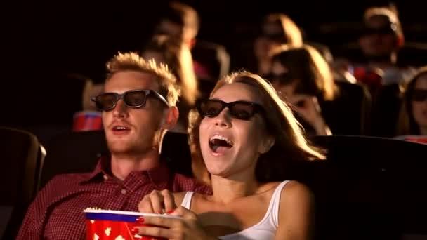 Eine Gruppe junger aufgeregter attraktiver, glücklicher männlicher Freundinnen, die Popcorn essen und 3D-Action-Kino genießen
