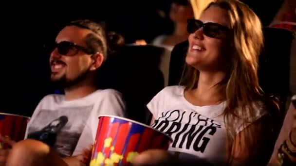 Eine Gruppe attraktiver junger aufgeregter, glücklicher männlicher Freundinnen isst Popcorn und genießt das 3D-4d-Actionkino