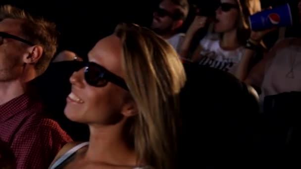 Egy csoport boldog fiatal vonzó, izgatott női férfi barátok eszik popcorn élvezi 3D 4d akciófilm mozi mozi