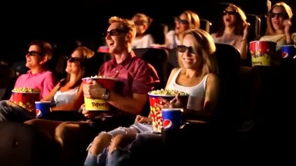 Eine Gruppe glücklicher attraktiver junger aufgeregter männlicher Freundinnen isst Popcorn und genießt das 3D-4d-Actionkino