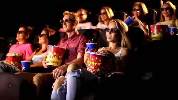 Egy csoport boldog izgatott fiatal vonzó férfi női barátok eszik popcorn élvezi 3D 4d akciófilm mozi mozi