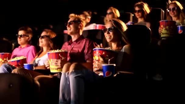 Eine Gruppe aufgeregter junger glücklicher attraktiver männlicher Freundinnen, die Popcorn essen und dabei 3D-Action-Kino genießen