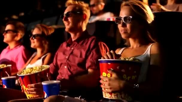 Eine Gruppe junger attraktiver, fröhlich aufgeregter männlicher Freundinnen genießt das 3D-4d-Actionkino beim Popcorn essen