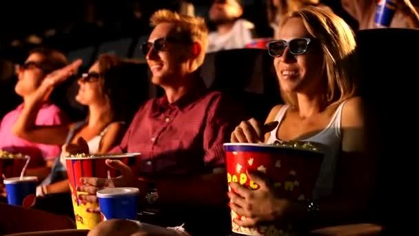 Eine Gruppe fröhlicher junger attraktiver aufgeregter männlicher Freundinnen genießt das 3D-4d-Actionkino und isst Popcorn