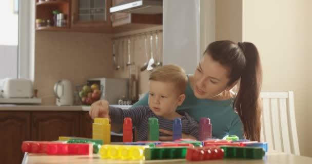 Mother Teaching Little Boy How to Count Using Colored Blocks and Using Educational Games