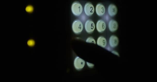 Finger zadání kombinace kódu na klávesnici s svítící tlačítka nastavení zabezpečení systému na záběr na červené