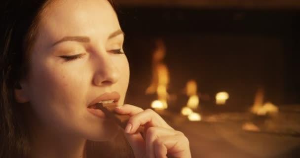 attraktive Weibchen beißen Schokoladendessert Augen zu und genießen den Geschmack drinnen am Kamin