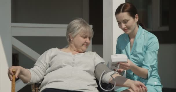 Kontrola krevního tlaku starší ženy ošetřovatelka se usmívá a stará se o staré lidi venku za slunečného dne na verandě v Terrasse na červeném fotoaparátu