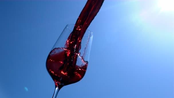 Vörösbor van öntés-ban-hoz egy pohár-val kék ég és napfény-ra háttér-ban lassú jelet ad