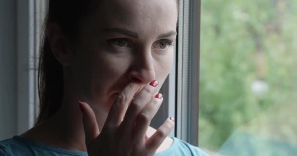 Frau pflückt Nase mit roten Nägeln am Fenster