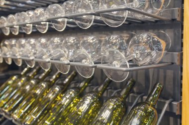 Glasses and bottles on a rack in the wine cellar. Alcohol