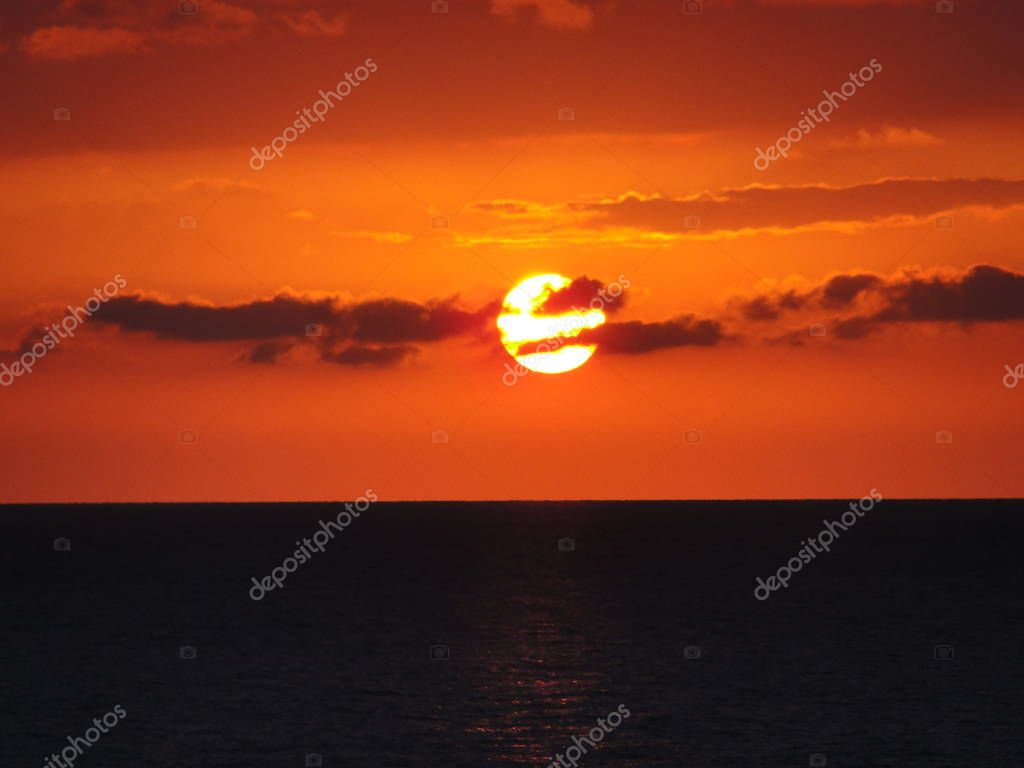 Beautiful red sunset. Natural Sunset Sunrise .Bright Dramatic Sky And Dark Ground. Landscape Under Scenic Colorful Sky