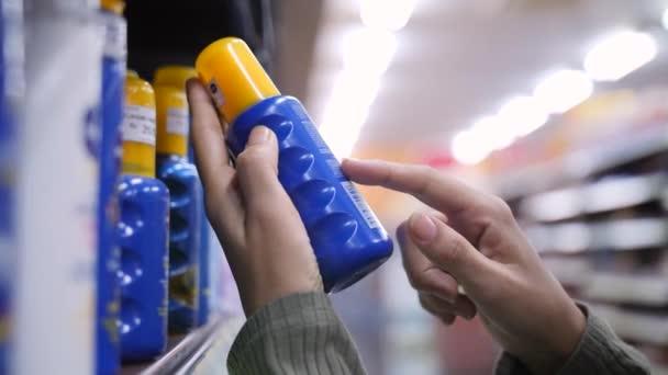 Mladá žena výběrem opalovacích krému a čtení složek na láhev v obchodě kosmetika Péče o tělo. 4k Slowmotion.