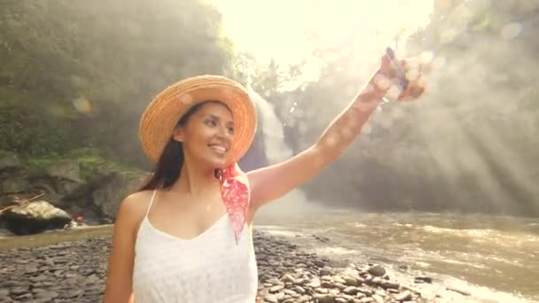Young Smiling Mixed Race Tourist Girl in White Dress and Straw Hat Making Selfie Photos Using Mobile Phone with Amazing Huge Jungle Waterfall. Lifestyle Travel 4K Footage. Bali, Indonesia.