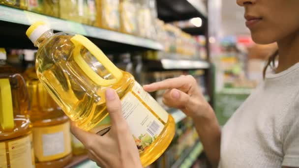 Mladá smíšený závod ženy výběr olivový olej v supermarketu. Zákazník, čtení složek popisku v obchodě. 4k.