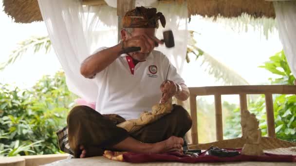 Holzschnitzer beim Schnitzen mit scharfen Werkzeugen auf Holzwerkstücken. traditionelle balinesische Statuettenherstellung. 4k. bali, indonesien.