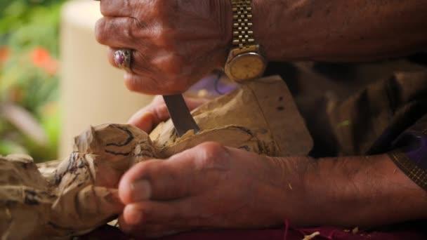 Řezbáře dělá Carving s ostrými nástroji na dřevěných obrobku. Tradiční balijské soška procesu. 4 k. Bali, Indonésie.