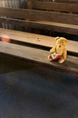 An old lost teddy bear on church pew in derelict old country church waiting for his owner to come back.