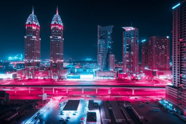 Beautiful view to Dubai and Sheikh Zayed Rd, United Arab Emirates. City skyline. Long exposure effect at night. Duotone retro wave neon noir lights color toned