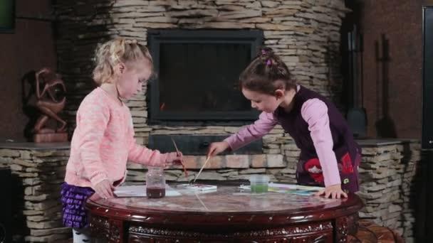 Děti kreslit obrázky. Malé dívky si hrají s barvami v obývacím pokoji