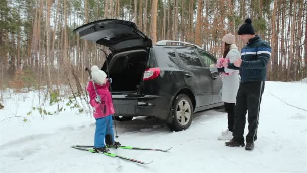 A family with one child spend fun time in nature. Family holiday in the winter forest.
