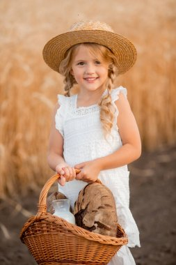 A little blonde girl in a wheat field with basket of home made bread. Environmentally friendly eco farm products concept.