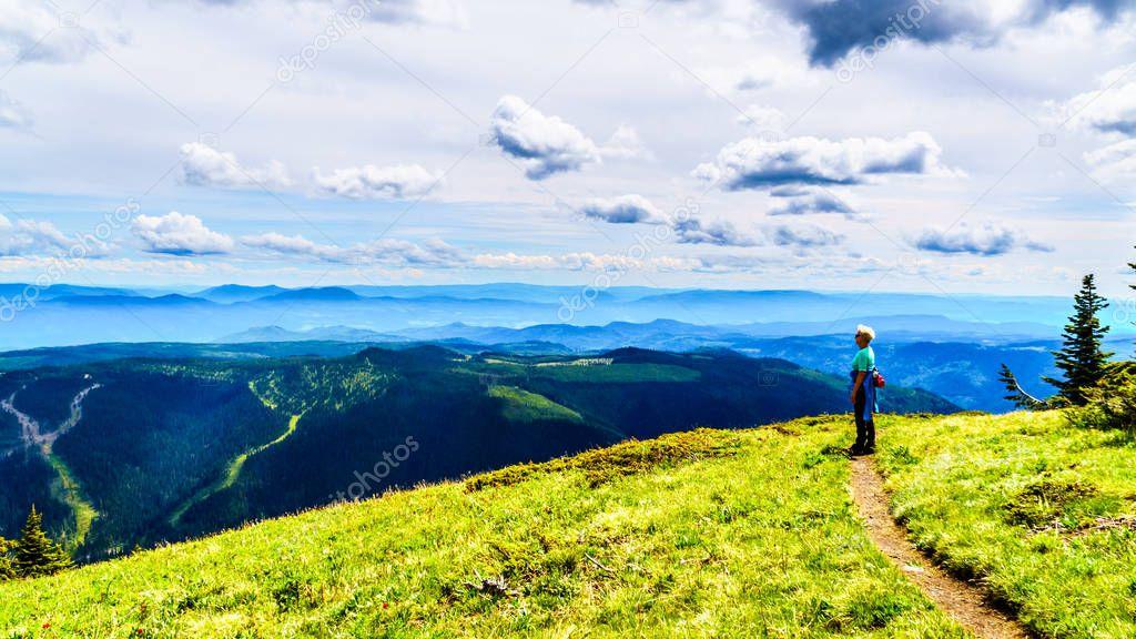 Senior Woman hiking on Tod Mountain near the alpine village of Sun Peaks in the Shuswap Highlands of British Columbia, Canada