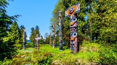 Colorful indigenous Totem Poles representing art and religious symbols of West Coast Indigenous peoples placed in Stanley Park in Vancouver, Canada