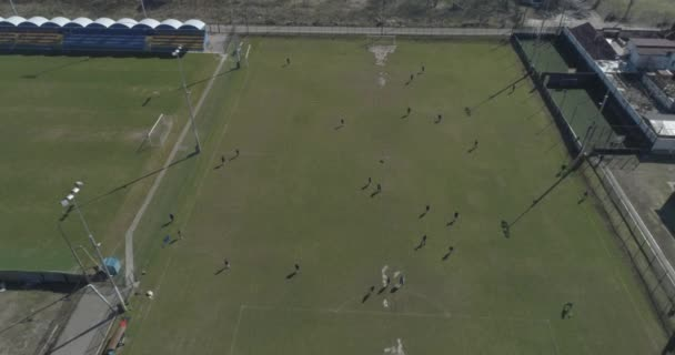 Aerial view of football or soccer field. Football players have training. 4K.