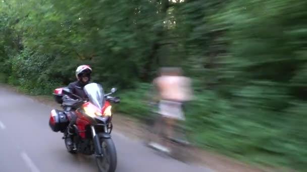 Mladý biker jezdíš na motorce přes lesní silnici. Stálý kardanní výstřel. 4k.