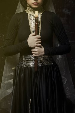woman in traditional armenian dress holding duduk in hands