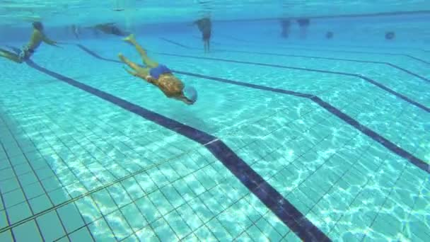 The teenager swims in the pool under the water.