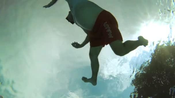 Teenager schwimmt im Pool unter Wasser.