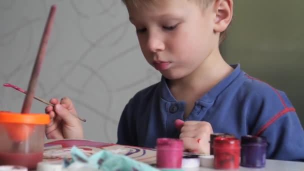fiú gyermek lelkesen festékek, akvarell, papír.
