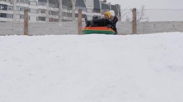 Kinder fahren im Winter mit einer Schlauchrutsche.